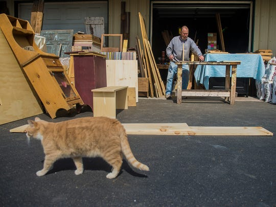Sonny Zeigler works outside at his Baltimore Pike shop as his cat, Buddy, strolls by. Zeigler doesn't maintain any online or social media presence for his furniture business.