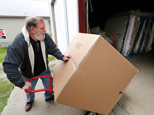 Owner Dick Mullen moves furniture pieces into the warehouse