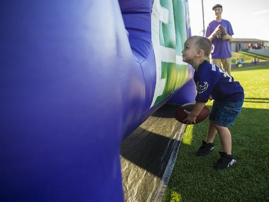 Josiah Lewis, 3, of Gettysburg, gets ready to put a football through the hole during an exercise at Play Like a Raven Football Clinic at Gettysburg Middle School on Tuesday. Nearly 220 campers participated in the event.