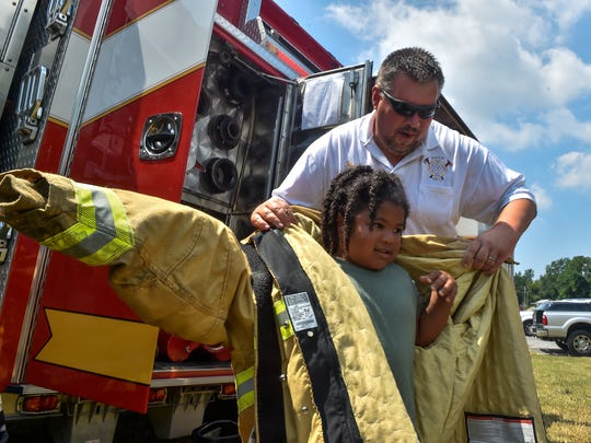 Chris Henson, president of the Marion Fire Department, helps Benito Garcia, 5, put on a fireman's jacket on Saturday, July 23, 2016 at Greene Township Park in Scotland, Pa.