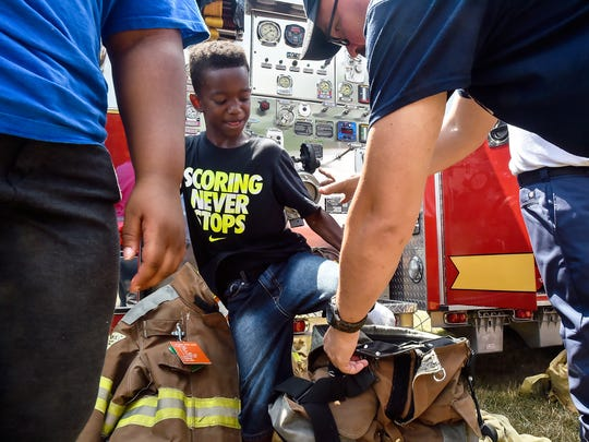 Jahrell Wallace gets some help from firefighters as he steps into a fireman's uniform during a cookout that was created by Chris Hock to bring in peace locals and first responders on Saturday, July 23, 2016 at Greene Township Park in Scottland, Pa.