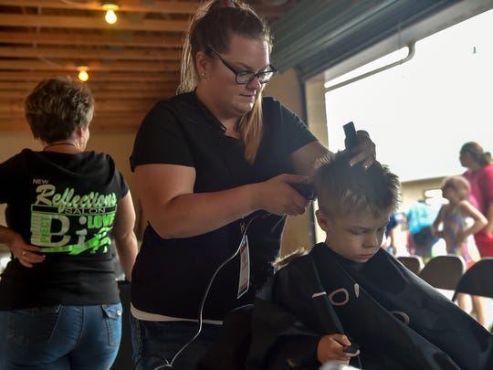 Jill Salmon cuts Exavear Yohe, 6, hair during Project Big Love on Saturday, July 30, 2016 in Mont Alto, Pa. Project Big Love is a not for profit event providing families with school supplies for the upcomming school year.