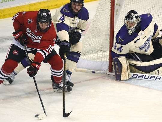 St. Cloud State's Mikey Eyssimont (19) protects the