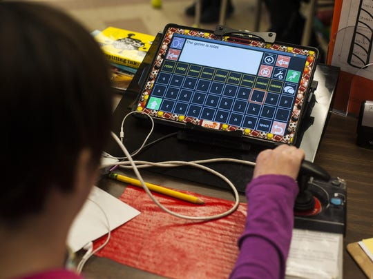 "Katie Hill uses her new speech device, a Zuvo made by Talk To Me Technologies and affectionately named Joy, to answer ""The genre is realistic fiction,"" on a reading comprehension quiz in her 6th grade class at Morningside Elementary."