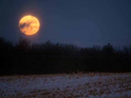 A Supermoon rises over a field in Warrington Township