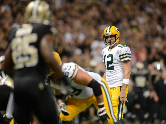 Packers quarterback Aaron Rodgers (12) surveys the