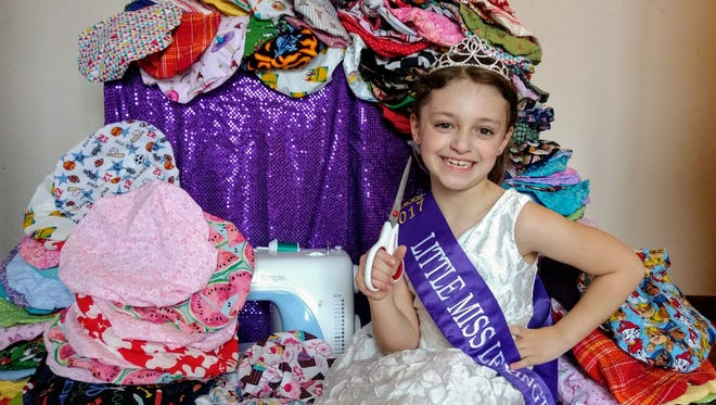 Little Miss Lexington Valarie Duffey poses with some of the caps she helped sew for sick children at Golisano Children's Hospital in Rochester, New York.