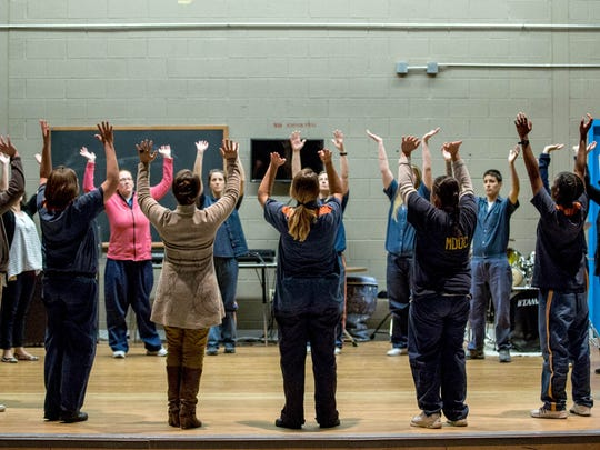 """Prisoners and facilitators gather on stage for The Ring before the rehearsal of Shakespeare in Prison's """"Othello"""" play in May 2016, at the Women's Huron Valley Correctional Facility in Ypsilanti. The Ring is when everyone who is participating in the play comes together before and after each rehearsal."""