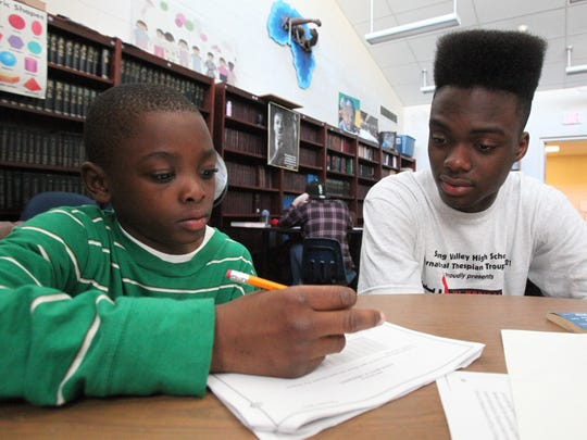 In this 2012 file photo, Spring Valley High School senior Florby Dorme helps Arlee Senat, 9, with his homework as part of the after-school program at the Martin Luther King Multi-Purpose Center in Spring Valley.