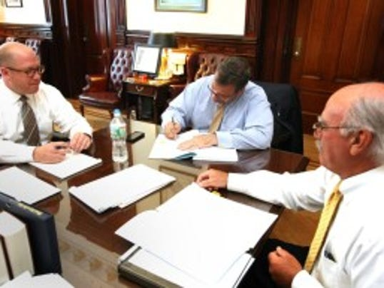 Gov. Chris Christie signs the 2015 state budget in his office Monday. (Tim Larsen/Governor's Office)