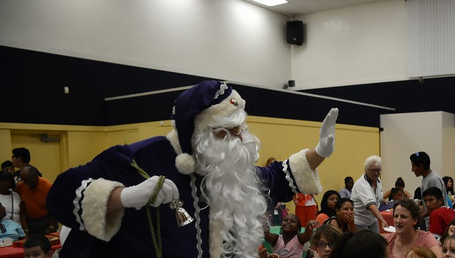 Santa Claus shows up, clad in purple instead of the traditional red.