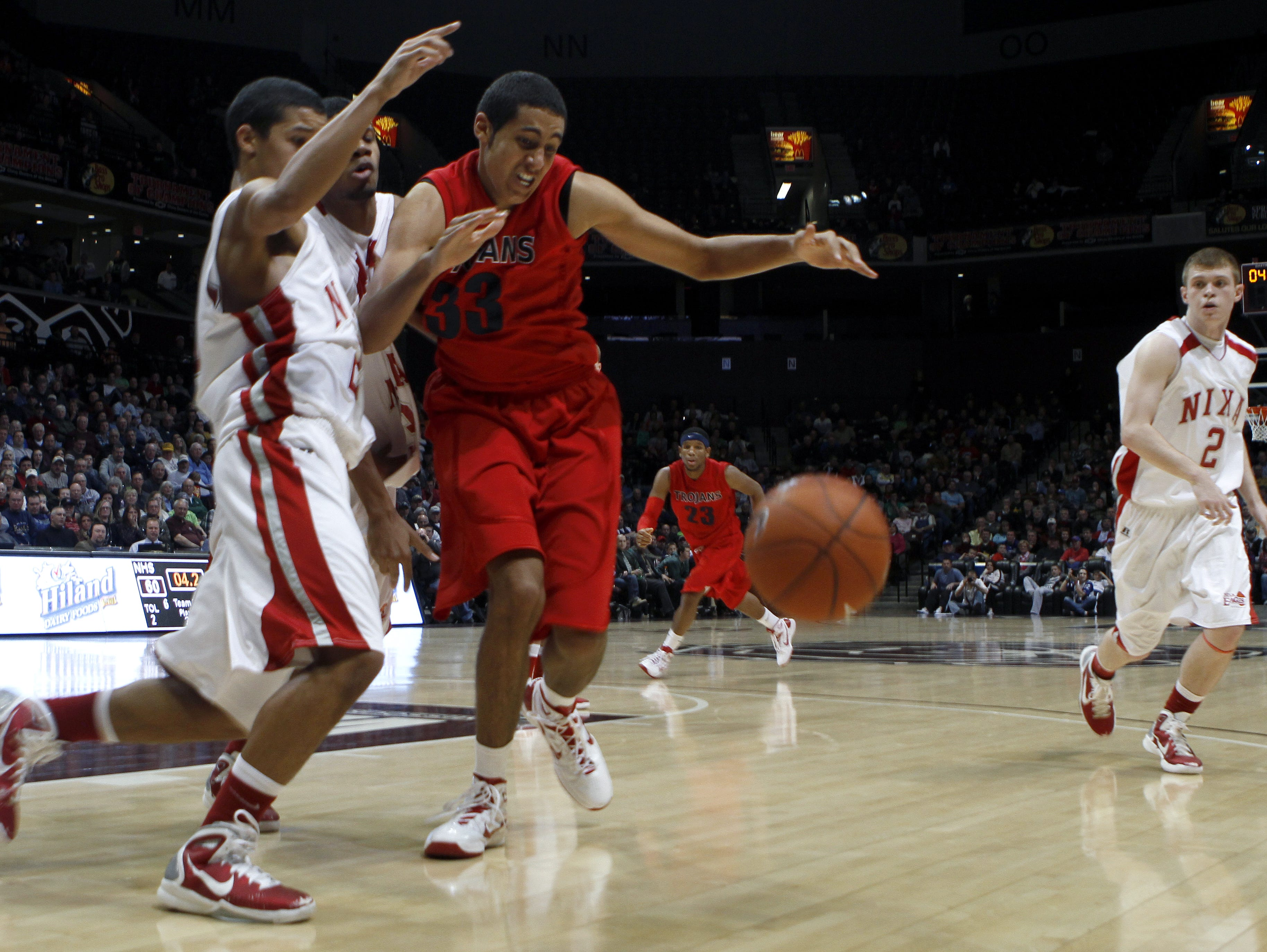La Verne Lutheran's Grant Jerrett (33) and Nixa's Jalen Norman (center) and Kameron Bundy scramble for a loose ball with 4.2 seconds left in a game during the 2011 Bass Pro Tournament of Champions at JQH Arena.