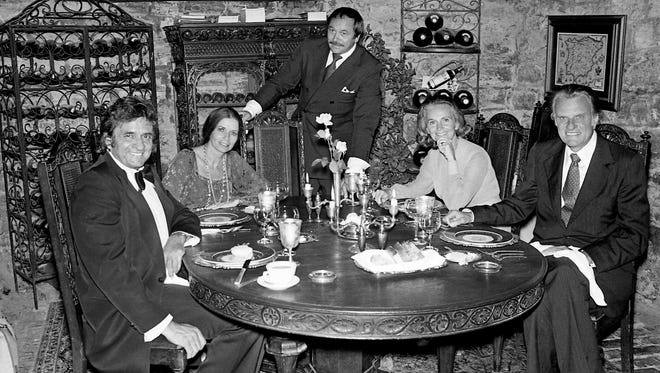 Johnny and June Carter Cash, left, and the Rev. and Mrs. Billy Graham enjoy supper at Mario's restaurant June 25, 1979, after the crusade. With them is their host Mario Ferrari, center.