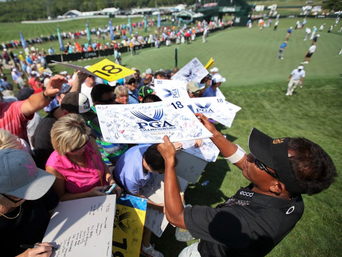 Golfer Thongchai Jaidee hands back an autographed flag to one of the spectators lining the route to the putting green at Valhalla. August 4, 2014