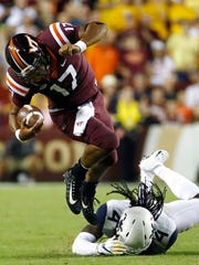 FILE - In this Sept. 3, 2017, file photo, Virginia Tech quarterback Josh Jackson, left, rushes past West Virginia cornerback Mike Daniels Jr. in the second half of an NCAA college football game in Landover, Md. Jackson threw for 235 yards and ran for 101 more in his debut against West Virginia, then led the Hokies in a shutout of Delaware. Last Saturday, he threw for 372 yards and five touchdowns,  four in the third quarter alone,  to beat East Carolina 64-17 for Tech's first 3-0 start since 2011 (AP Photo/Patrick Semansky, File)