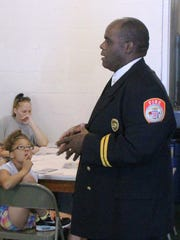 Robert Tipler of the Jackson Fire Department talks to children about the importance of fire safety during the Back 2 School Bash on Saturday at Blairs Chapel CME Church in Jackson.