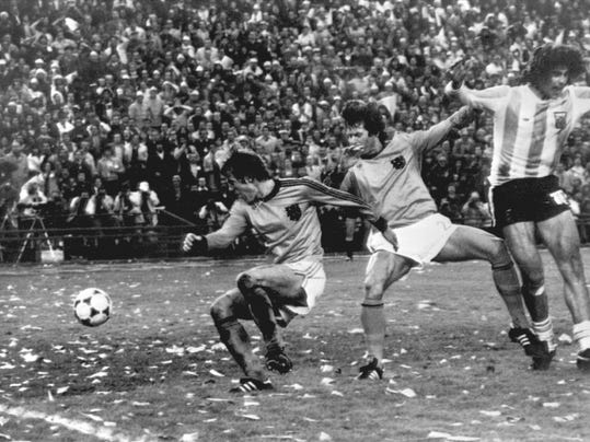 FILE - In this Sunday, June 25, 1978 file photo, Mario Kempes of Argentina, right, celebrates, after scoring Argentina's second goal against the Netherlands, during their World Cup final soccer match, at the River Plate Stadium, in Buenos Aires, Argentina. At left is Dutch player Ruud Krol, and Poortvliet at centre.  On this day: Argentina wins its first World Cup in front of a confetti-laden crowd. (AP Photo/File)