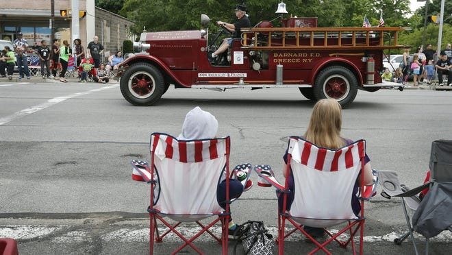 A last ride for past firefighters Jerry Dunst at the wheel and Mike Pospula on the 1928 first pumper from Barnard Fire Department during the opening parade for the last Barnard Firemen's Carnival in Greece, which has been held for 89 years.