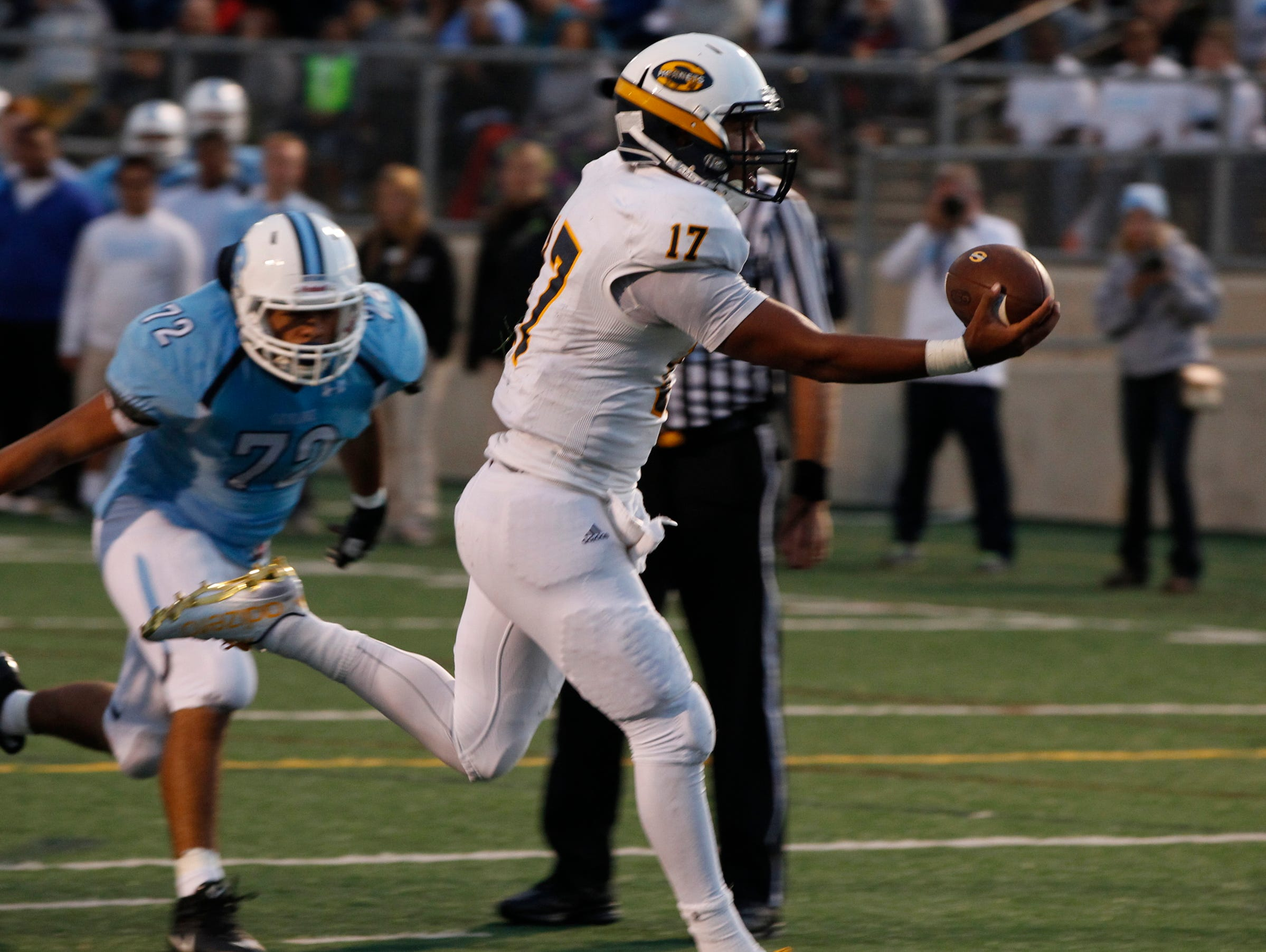 Saline quarterback Josh Jackson holds the ball out as he crosses the goal line for a touchdown and 17-0 lead over Ann Arbor Skyline high school on Friday, September 11, 2015, in Ann Arbor.