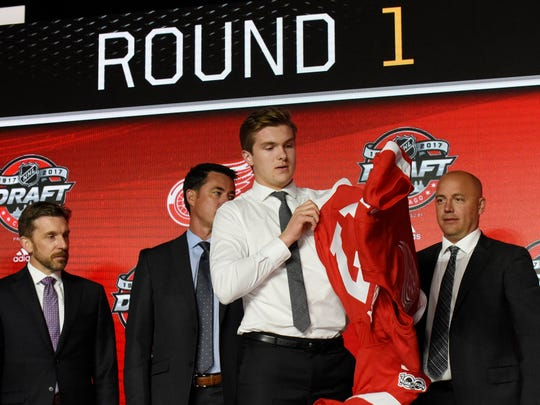 Michael Rasmussen puts on a team jersey after being selected as the No. 9 overall pick to the Detroit Red Wings in the first round of the 2017 NHL draft at the United Center.