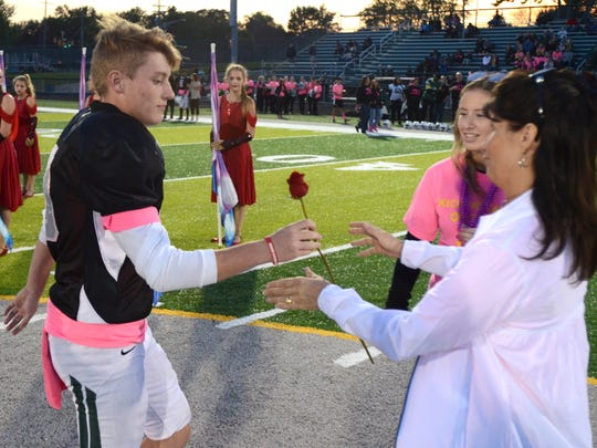 Nick O'Shea gives his mother Lisa a rose on Senior Night at West Bloomfield High School on Oct. 20, 2017. Nick's sister, Jessie, is pictured right. Nick's father, Dan, died of a heart attack on Oct. 10.