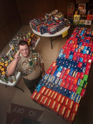 Michael Arechavala posed for a photo with some of the food donations he collected for his Eagle Scout project. Arechavala is a three-sport athlete at Audubon High School and on Sunday will earn his Eagle Scout honors for his service project. Michael set out to collect 500 food items for the Logan Memorial Presbyterian ChurchÕs food bank. He ended up collecting more than 6,100 items instead.