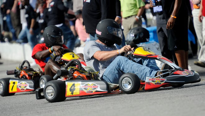 Titans quarterback Jake Locker speeds past Titans safety Bernard Pollard out of the pits during his celebrity Go-Karting Challenge on Tuesday at Fairgrounds Speedway.