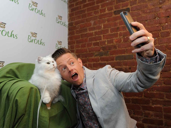 "IMAGE DISTRIBUTED FOR FANCY FEAST - Chef Richard Blais takes a ""selfie"" with the iconic Fancy Feast cat while hosting the Fancy Feast Broths launch party at the Tasting Table Test Kitchen in New York, Tuesday, July 22, 2014. (Photo by Diane Bondareff/Invision for Fancy Feast/AP Images)"