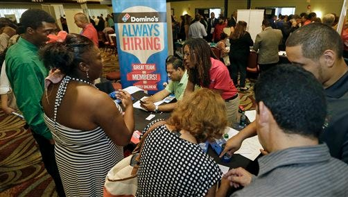In this photo taken Wednesday, July 15, 2015, job seekers listen as Kaysara Mandry, center, talks about job opportunities at the Domino's booth during a job fair in Miami Lakes, Fla.  U.S. hiring slowed sharply and previous job gains were revised lower amid a broad slowdown in the global economy. The Labor Department says employers added just 142,000 jobs in September 2015 as manufacturers and oil drillers shed workers.