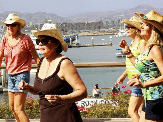 From left, Leanne Rose, Xochitl McDonald, Leanne Roth and Susi Gonzalez enjoy line-dancing Saturday on a patio at Ventura Harbor Village during the Rock the Dock concert Saturday.