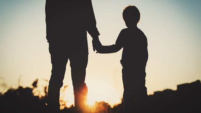 Silhouette of father and son holding hands