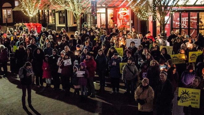 Dozens hold a vigil outside Burlington City Hall on Church Street Monday night in support of refugee resettlement in Vermont.