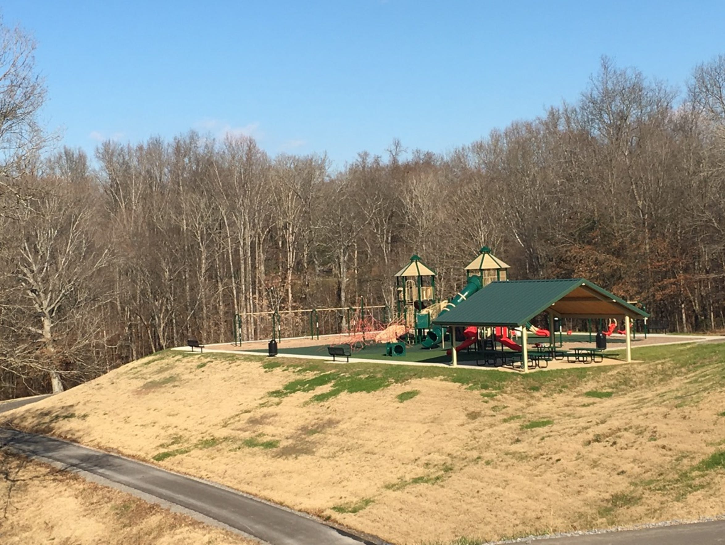 A paved walking trail winds around the main playground