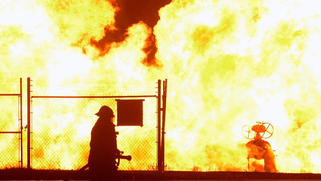 A Fort Smith firefighter moves in closer to a gas main fire on Wednesday night at the corner of Massard Road and Zero Streets.