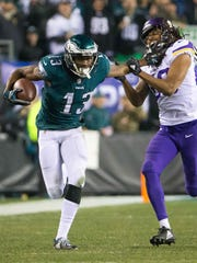 Eagles wide receiver Nelson Agholor stiff arms a defender