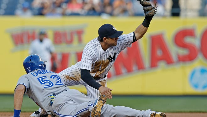 Yankees second baseman Brian Roberts shows the ball to the umpire after pitcher David Phelps picked off the Blue Jays' Melky Cabrera  during Thursday night's game. Cabrera was called safe on the play, but Yankees manager Joe Girardi had it reversed with a replay challenge.