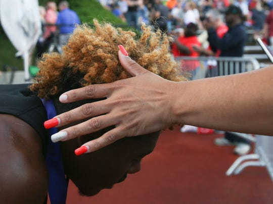 D'Wayne Eskridge's mother Monique Johnson rubs her hands through his hair after his last win at the IHSAA boys state track and field finals on June 4, 2016.