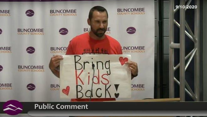 Ben Whitmire made his thoughts clear with a sign during a meeting of the Buncombe County Schools Board of Education last week.