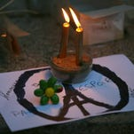 Candles are put on a peace sign combined with the Eiffel Tower at a temporary memorial for the victims of the Paris attacks. French President Francois Hollande vowed to attack the Islamic State without mercy. The group claimed responsibility for orchestrating the deadliest attacks on France since World War II.