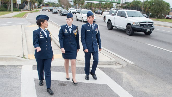 """Air Force Junior ROTC Cadet Col. Jasmaine Roberge, left to right, Cadet Lt. Col. Grace Overholtz, and Cadet Chief Master Sergeant Kyle Muldoon walk along Gulf Breeze Blvd. in front of Gulf Breeze High School on Thursday, November 9, 2017.  These seniors created a """"Don't Drive Distracted"""" campaign to help lessen the amount of vehicle accidents that occur along this busy stretch of road predominantly before and after school."""