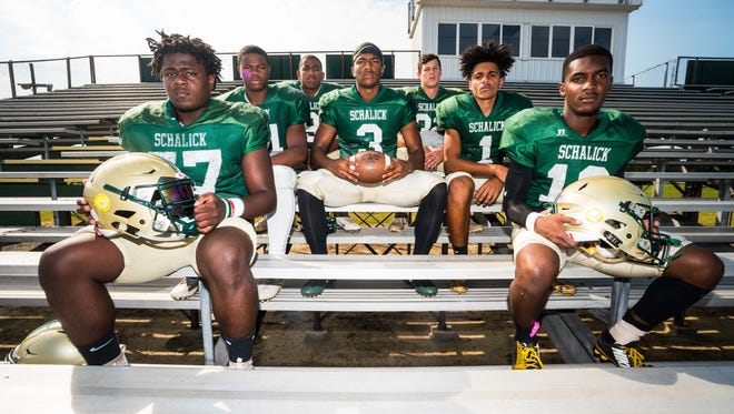 Schalick's CJ Holmes (3) has the support of his teammates Tyree Newman, Tyreese Snipe, Jaylen Hoover, Ethan Long, Javon Spann and Kason Barrett after losing his father Cedric and fellow assistant Coach Michael Hars.