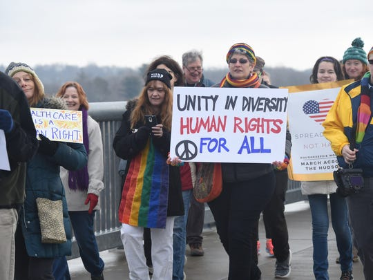 Marchers holding signs during the Poughkeepsie Women's March Across the Hudson at the Walkway Over the Hudson State Historic Park on Jan. 21.