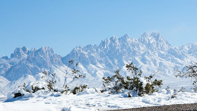 "Kim Aline, who just moved to Las Cruces from San Diego in January, takes a picture of the snow covered Organ Mountains on Monday just off of Sonoma Ranch Blvd. ""The should make a scenic-view post here,"" said Aline. ""It is beautiful."""