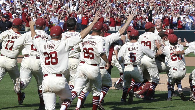 Arkansas pitcher Zach Jackson, right, is swarmed by teammates as he holds up one finger after a super regional of the NCAA college baseball tournament in Fayetteville, Ark., Sunday, June 7, 2015. Arkansas defeated Missouri State 3-2.