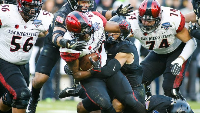 Dec. 23: San Diego State running back Rashaad Penny (20) tries to elude Army defenders Elijah Riley (23) and Jaylon McClinton (7) during the second half.