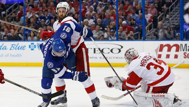 Wings goaltender Petr Mrazek catches the puck as Wings' Kyle Quincey upends Tampa Bay's Steven Stamkos in Game 5 on Saturday.