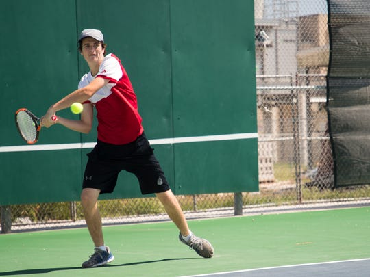 Ray High School tennis's George Webster warms up during