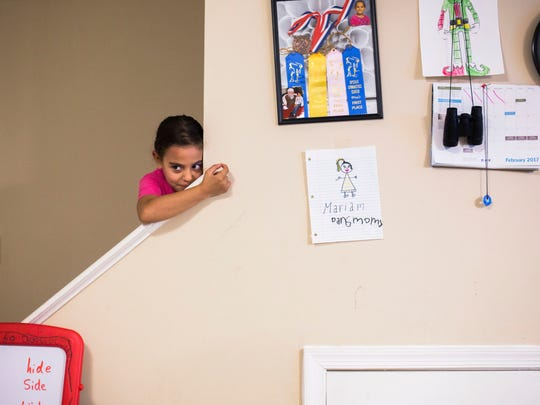 Mariam Shukri, 6, procrastinates on doing her homework and spies on her parents sitting in the family's living room on Thursday, February 2, 2017 in Clemson.