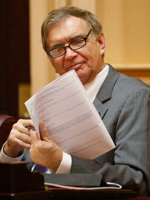State Sen. Emmett Hanger, R-Augusta, looks over the bill book during the Senate session at the Capitol in Richmond, Va., Monday, Feb. 12, 2018. The Republican-controlled Virginia General Assembly appears to be on track to defeating every measure aimed at preventing the kind of violence that broke out at a white nationalist rally in Charlottesville last summer, (AP Photo/Steve Helber)