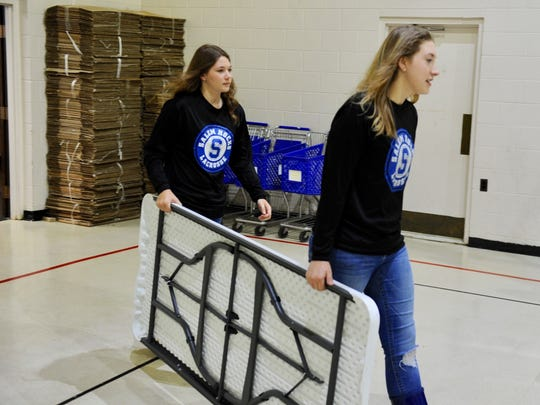 Olivia Minehart (left) and Madison Sopha carry tables in preparation for food to be delivered and sorted.